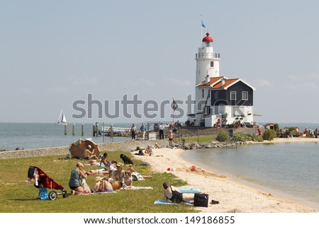 "MARKEN - JULY 15: People are sunbathing and playing in the water at the ""Paard van Marken"" lighthouse in Marken, the Netherlands, on July 15, 2013. - stock photo"