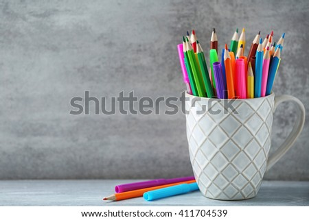 Markers in pencils in ceramic cup in front of wall background