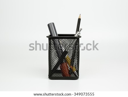 Markers, pen, pencil in black basket isolated on white background - stock photo