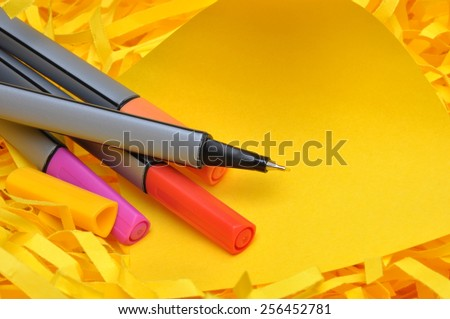 Markers with yellow sticky note on shredded paper - stock photo