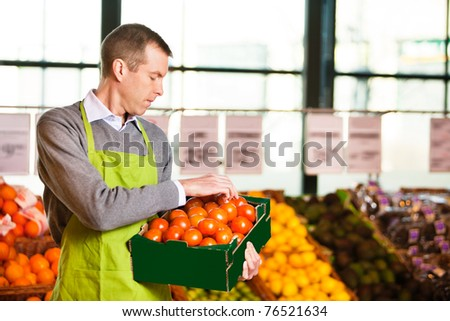 Market assistant wearing apron with holding box of tomatoes in the supermarket - stock photo