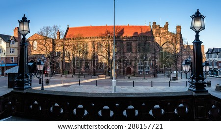 Market square in Chester UK. Late evening light illuminating the red roof top of old building framed by the street lamps. - stock photo