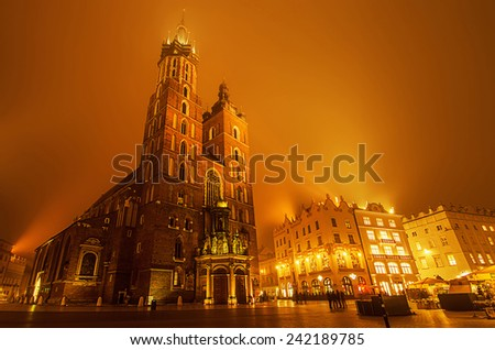 Market square in Cracow at misty night with St. Mary's Basilica with golden sky - stock photo