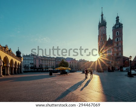 Market square in Krakow at sunrise. Mariacki Cathedral. Poland - stock photo
