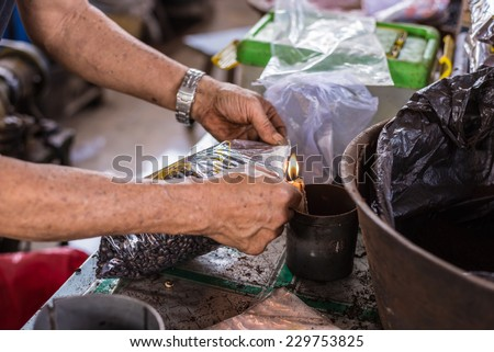 Market vendor sealing bag of freshly roasted black coffee beans for sell in indonesian market (Sulawesi). Unrecognizable person, arms and hands only shown. - stock photo