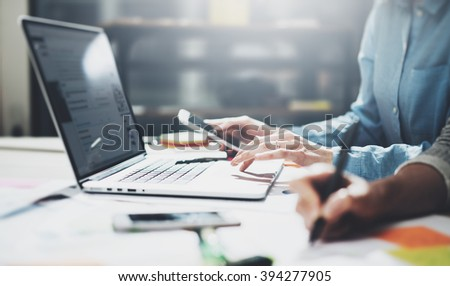 Marketing analyze team meeting.Young businessmans crew working with new startup project in modern loft.Generic design notebook on wood table.Smartphone hands.Horizontal, film effect,blurred background