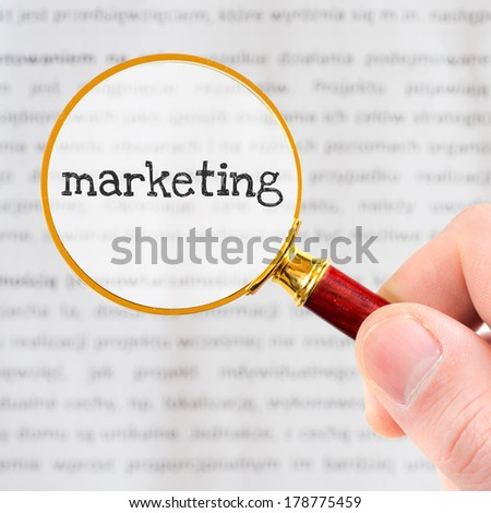 Marketing. Hand, holding classic styled magnifying glass with word Marketing - stock photo