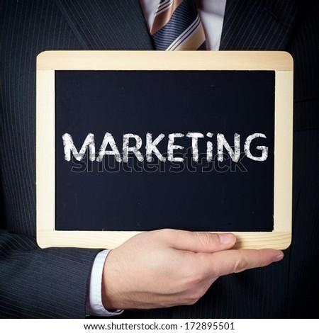 Marketing handwritten on blackboard which holding man - stock photo
