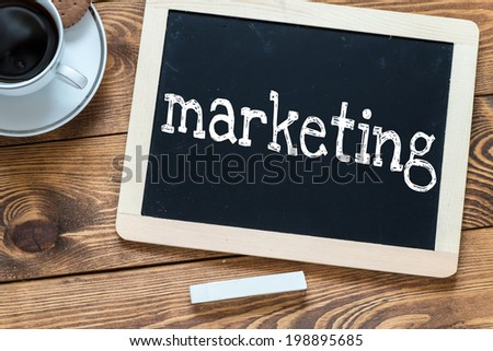Marketing handwritten with white chalk on a blackboard, cup of coffee and biscuit on a wooden background - stock photo