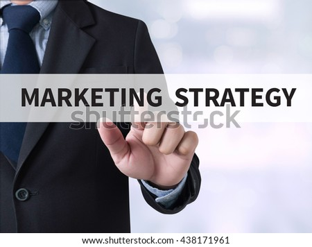 MARKETING STRATEGY Businessman touching a touch screen on blurred city background - stock photo