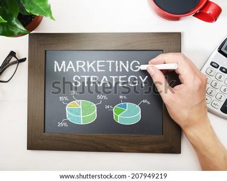 Marketing strategy sketched on a little black chalkboard - stock photo