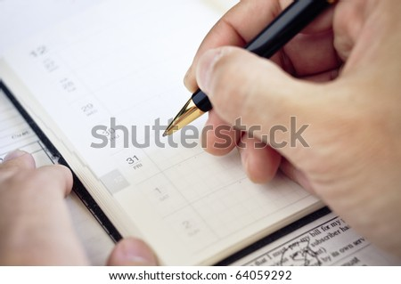Marking calendar in organizer - stock photo