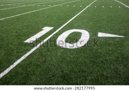 Markings for the ten yard line on an American football field indicate the distance to the goal line. - stock photo