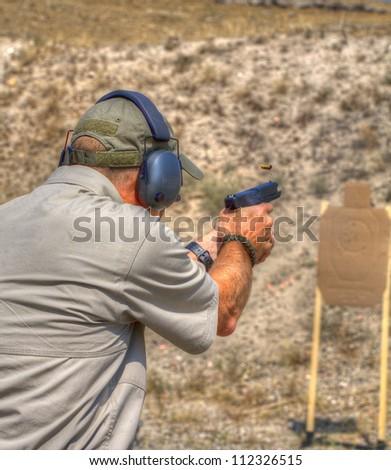 Marksman practicing at the range with a polymer handgun - stock photo