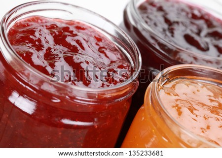 Marmalade jars with jam made from strawberries, cherries and apricots - stock photo