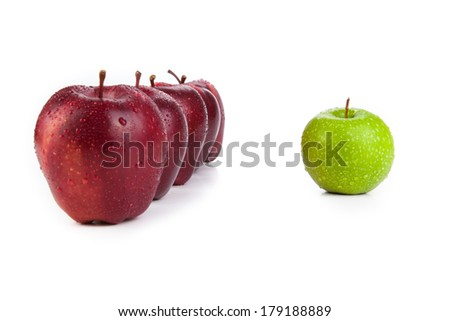 maroon apples lined up in a row and green apple closeup on a white background