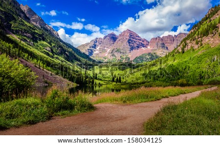 Maroon Bells in day light with clouds - stock photo
