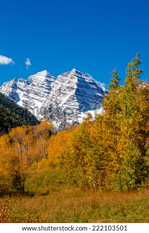 Maroon Bells mountain peaks covered with freshly fallen snow near Aspen Colorado on sunny fall morning - stock photo