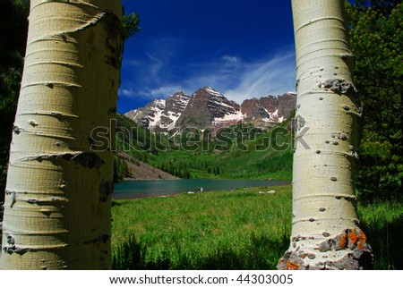 Maroon Bells Mountain Peaks in the summer at Maroon Lake and two hikers on edge of lake framed by Aspen Trees. - stock photo