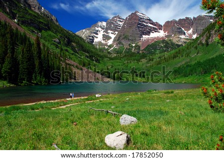 Maroon Bells Mountain Peaks in the summer with Maroon Lake in foreground and two hikers strolling on the edge of lake - stock photo