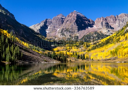 Maroon Bells mountain peaks reflecting in Maroon Lake on early autumn morning with bright blue skies and changing yellow Aspen trees on mountain slopes - stock photo