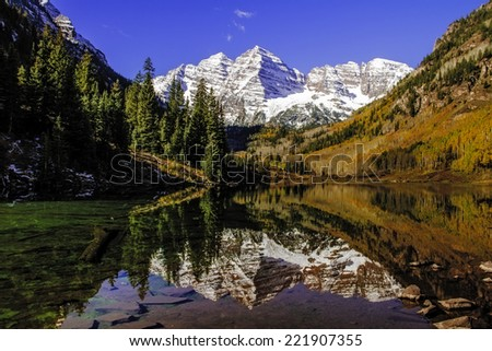 Maroon Bells peaks in the Elk Mountains reflecting on Maroon Lake in early morning sunlight - stock photo