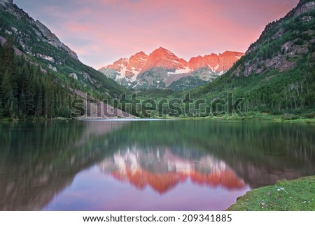 Maroon Bells snow capped peaks reflected in a lake at sunrise - stock photo