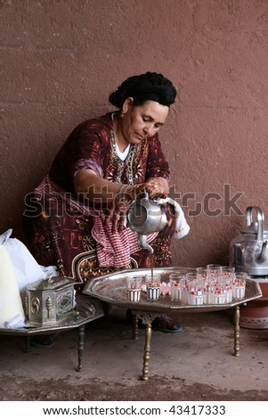 MARRAKECH, MOROCCO - AUGUST 8 : A Berber woman performs the traditional ceremony of making mint tea on August 8, 2008 in Marrakech, Morocco. This was a demonstration of Berber life made to tourists. - stock photo
