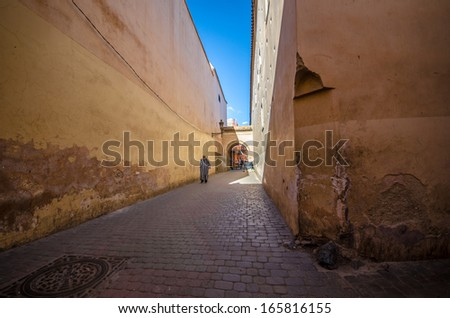 MARRAKECH, MOROCCO - MARCH 19: unidentified man walks in a streets of the old Medina of Marrakech, Morocco, on march 19, 2013. The old Medina is full of Historical Palaces and Mosques - stock photo