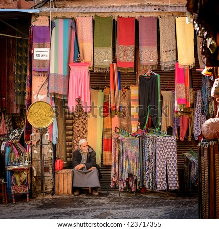 MARRAKECH, MOROCCO - NOVEMBER 04, 2015: A man sitting at his fabric shop in the souk of Marrakech in Morocco. - stock photo