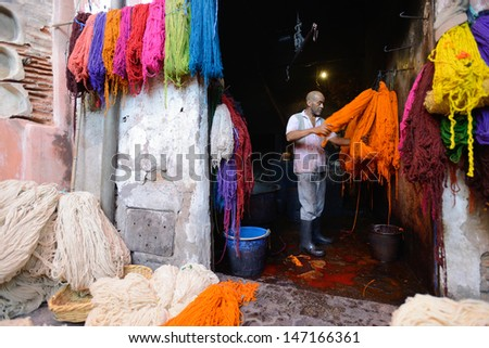 MARRAKESH - JULY 09: Unknown man dyeing fabric in a market (souk), July 09, 2013 in a Marrakesh, Morocco. The market is one of the most important attractions of the city Marrakesh, Morocco - stock photo
