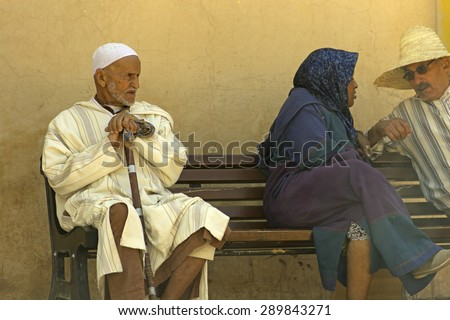 MARRAKESH, MOROCCO - APRIL 25: A stylish old Moroccan man in a long white gown seating in a bench in the street in Marrakesh, in Morocco, on April 25th, 2015 - stock photo