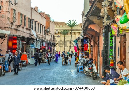 MARRAKESH, MOROCCO, APRIL 2, 2015: People walk in old alley near Jemaa el-Fnaa square - stock photo