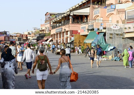MARRAKESH, MOROCCO - AUGUST 24: Tourists visiting Djemaa el Fna - market place in Marrakesh's medina quarter on 24 August 2014 in Marrakesh, Morocco. Djemaa el Fna is a UNESCO world heritage site.
