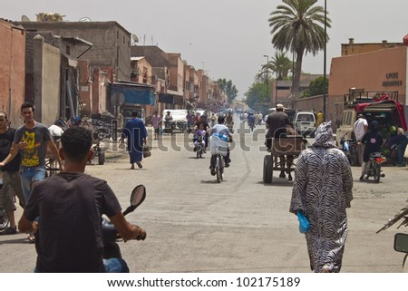 MARRAKESH, MOROCCO - AUGUST 8: Unidentified people at a street on August 8, 2010 in Marrakesh, Morocco. Marrakesh, with a population of 900,000 is the most important former imperial city in Morocco. - stock photo