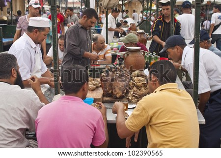 MARRAKESH, MOROCCO - AUGUST 8: Unidentified people eat at a stall at the Jema el Fna Square in Marrakesh on August 8, 2010 in Marrakesh, Morocco. The square is part of the UNESCO World Heritage. - stock photo