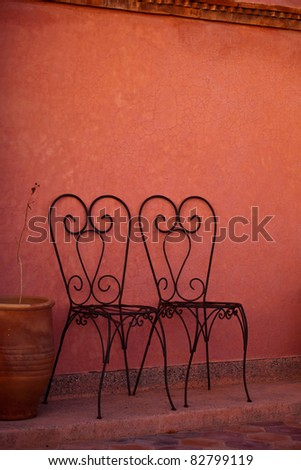Marrakesh, Morocco: Colorful wall and heart shaped iron chairs, Marrakesh, Morocco - stock photo