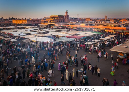 MARRAKESH, MOROCCO- DECEMBER 28: Crowd in Jemaa el Fna square in late afternoon on December 28, 2014 in Marrakech, Morocco. People blur to imply their movements. - stock photo