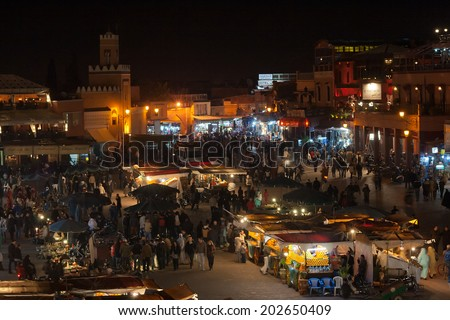 MARRAKESH, MOROCCO - JAN 29: People shopping in the evening at famous Marrakesh square Djemaa el Fna on January 29, 2010 in Marrakesh, Morocco. The square is part of the UNESCO World Heritage.  - stock photo