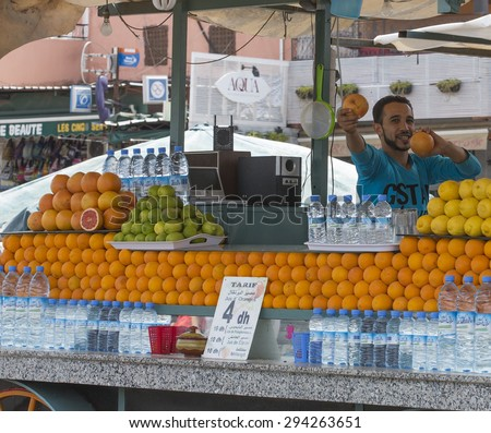 MARRAKESH ,MOROCCO - JUNE 4: Unidentified man selling orange juice at the Djemaa el Fna square in Marrakesh on June 4, 2013 in Morocco. In 2009 the medina got part of UNESCO World Heritage.  - stock photo