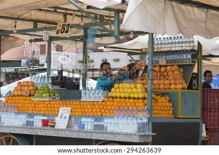 MARRAKESH ,MOROCCO - JUNE 4: Unidentified people selling orange juice at the Djemaa el Fna square in Marrakesh on June 4, 2013 in Morocco. In 2009 the medina got part of UNESCO World Heritage.  - stock photo