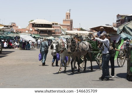 MARRAKESH, MOROCCO - JUNE 3: Unidentified people visit the Djemaa el Fna Square on June 3, 2013 in Marrakesh, Morocco. The square is part of the UNESCO World Heritage - stock photo