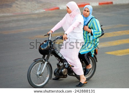 Marrakesh, Morocco - March 2006: Two women in traditional dress on a  motorcycle in the city center - stock photo