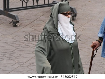 MARRAKESH, MOROCCO - OCTOBER 8: A muslim woman in traditional dress in Jemaa el Fnaa Square, Marrakesh, Morocco on the 8th October, 2015. - stock photo