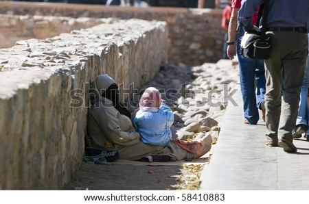 MARRAKESH, MOROCCO - OCTOBER 27: Beggar with her child near the Koutoubia mosque on October 27, 2008 in Marrakesh, Morocco. - stock photo