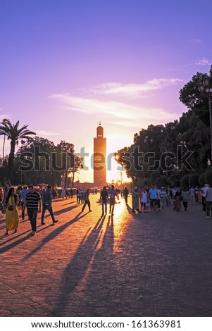 MARRAKESH, MOROCCO - OCTOBER 23: Unidentified people walk at the Jemaa el Fna Square in front of the Koutoubia mosque at sunset on October 23, 2013 in Marrakesh, Morocco.  - stock photo