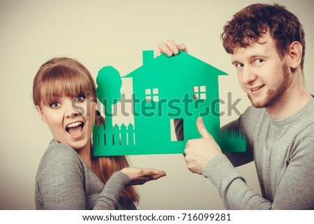 Marriage home love ownership property design concept. Cheerful pair celebrating their future. Young girlfriend boyfriend laughing preparing house model for family.