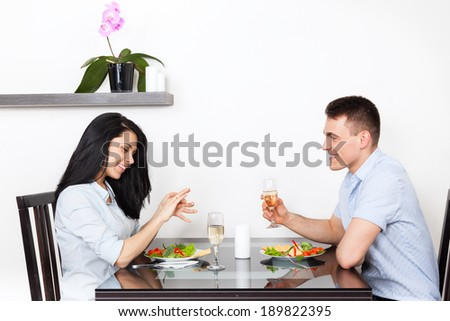 marriage proposal, woman putting an engagement ring on finger, young happy couple dinner romantic date at restaurant, sitting at table celebrating - stock photo