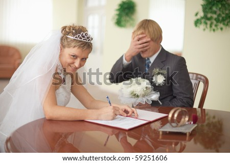 Marriage registration. The bride is happy. The groom in grief. - stock photo