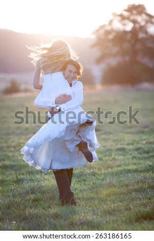 Married couple acting free and happy. The groom carries his bride on his shoulder. - stock photo